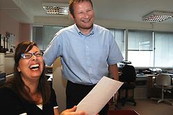 Office workers sharing a joke in office UK