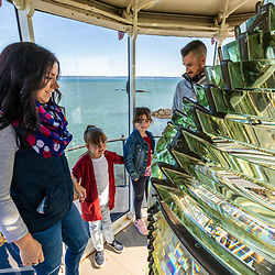 A couple and their two young girls in the West Quoddy Head Lighthouse in Lubec, Maine.