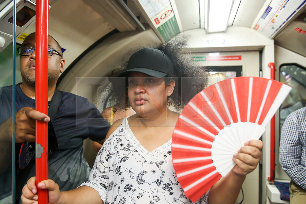 © Licensed to London News Pictures. 25/07/2019. London, UK. A tourist from Madagascar uses a hand held fan to cool down while travelling on Central Line. According to the Met Office, today will be the hottest day of the year and temperatures are expected to break records. <br /> <br /> ***Permission Granted***<br /> <br /> Photo credit: Dinendra Haria/LNP