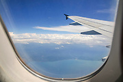 Elevated view of the Mediterranean Sea and clouds as seen through the window of an Airbus A320-200 plane