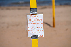 Portobello, Scotland, UK. 8 May 2020. Images from Friday afternoon during Covid-19 lockdown on promenade at Portobello. Promenade and beach were busier than in recent weeks due to warm sunny weather and the fact that several cafes and takeaway food shops are now open. Police patrols were low key. Pictured; sign on volleyball posts stating not to be used. Iain Masterton/Alamy Live News