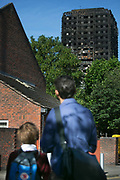 A father and son on their way to school look back on the tower June 16th 2017, London, United Kingdom. Grenfell Tower burned out after a catastophic fire killing more than 58 people. The tower caught fire early Wednesday morning and final casualty figueres may end up to be many more with police not expecting to be able to find and recover all bodies and to find all missing people. No fire sprinkler in place and cheap cladding made with plastic is so far blamed for the ferocious fire.
