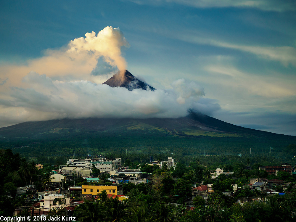 25 JANUARY 2018 - DARAGA, ALBAY, PHILIPPINES:  The Mayon volcano vents before a larger eruption Thursday night with the town of Daraga in the foreground. The Mayon volcano continued to erupt Thursday. The airport in Legazpi is closed until at least 31 January 2018. More than 60,000 people have been evacuated because of the volcano.     PHOTO BY JACK KURTZ