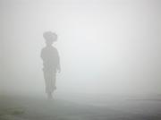 Woman walking in the mist near Kigali, Rwanda