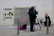 London, UK. Saturday 23rd February 2013. TV reporting from the site of the Wood Green Banksy in North London. The iconic artwork was removed from this site and will go on sale in Miami and is expected to reach an estimated £500,000. Local people are protesting and campaigning to stop the ale.