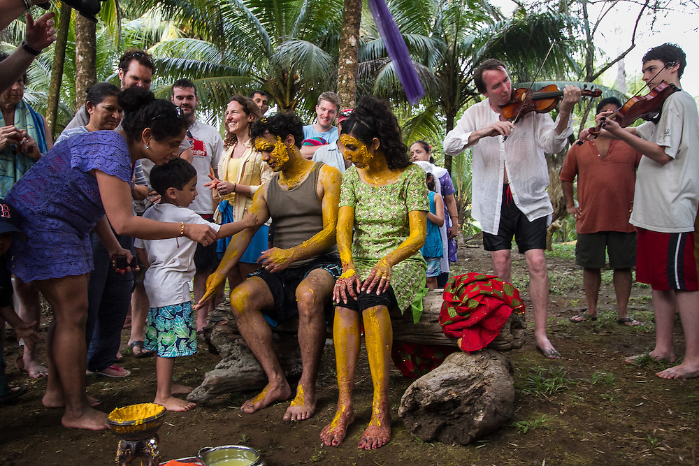 Ojochal, Costa Rica: Surrounded by friends and family, filmmaker Sharat Raju and filmmaker, lawyer, and community activist Valarie Kaur are bathed in turmeric paste as part of their wedding rituals near her parents home in Costa Rica. They live in Los Angeles, California.