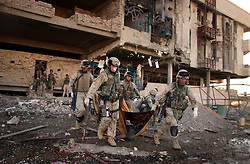 The Marines of Charlie Company 1st BN 4th Marines carry the bodies of enemy dead from their position during the assault on the outskirts of Najaf's Old City in preparation for the final push on the Imam Ali Shrine held by fighters from the Moqtada al-Sadr-led Mehdi Army during the Battle of Najaf on August 26, 2004.<br />