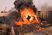 Burning oil well in the Rumaila Oil Field in southern Iraq. The wells were ignited by retreating Iraqi troops when the US and UK invasion began in March 2003. Seven or eight wells were set ablaze and at least one other was detonated but did not ignite. The Rumaila field is one of Iraq's biggest oil fields with five billion barrels in reserve. Rumaila is also spelled Rumeilah.