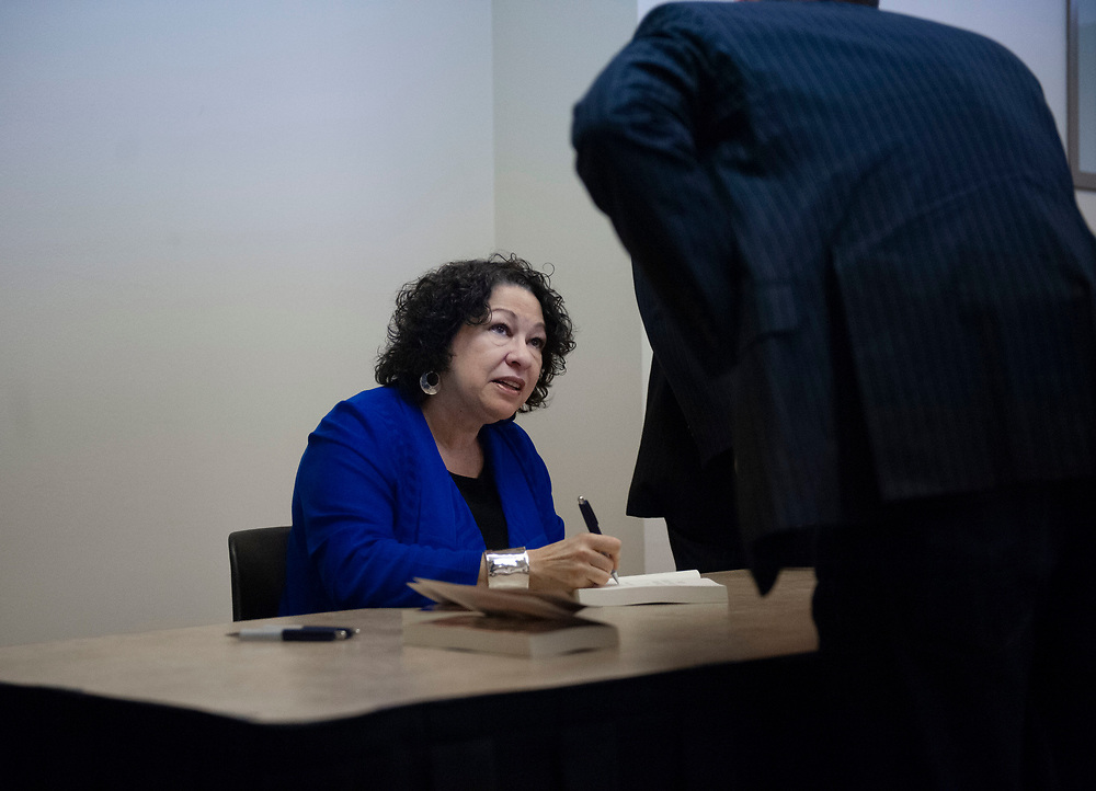 """Associate justice of the Supreme Court of the United States Sonia Sotomayor speaks signs copies of her book, """"My Beloved World,"""" before then leading a three-judge panel Monday, Jan. 27, 2014 for the final round of the UC Irvine School of Law's fourth annual Experian/Jones Day Moot Court Competition."""