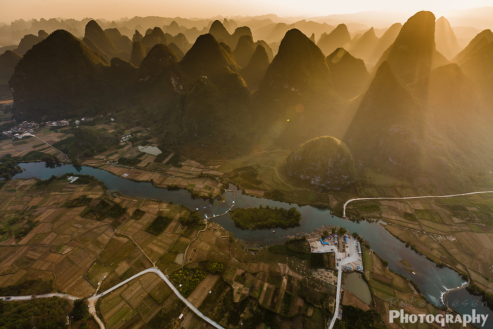 Aerial view of Li River and karst formation with sunlight streaming between the steep peaks, southern China