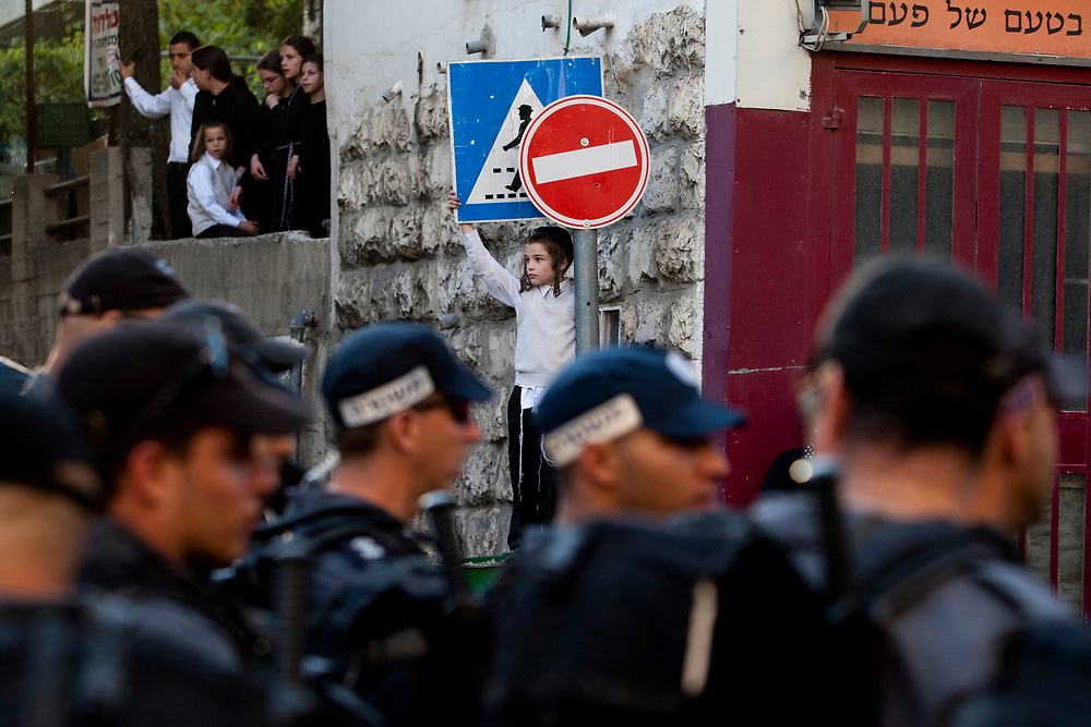 An ultra-Orthodox Jewish child (C) watches Israeli policemen during a demonstration on Neviim Street, a central thoroughfare in Jerusalem on July 16, 2011. Close to a thousand ultra-Orthodox Jewish men held a demonstration against the desecration of Shabbat,<br /> marking one hundred weekends to the opening of the Karta municipal parking lot in the capital.