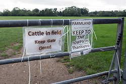 Field next to the Thames Path National Trail where it runs between Pangbourne and Purley near Reading. Cows are normally grazing the field shown so warning signs to walkers. UK 2020