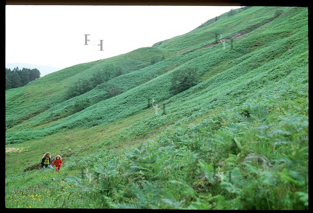 Girl and mom hike hills of Clachaig Gulley, Harry Potter's Prisoner of Azkaban movie film site for Hagrid's Hut; Glencoe, Scotland.