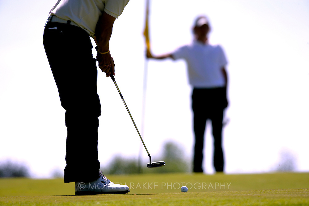 Man putting the ball at golf green