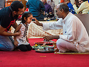 05 SEPTEMBER 2015 - BANGKOK, THAILAND:  A Hindu priest anoints people during Janmashtami services at the Vishnu Temple in Bangkok. Janmashtami is the annual celebration of the birth of the Hindu deity Krishna, the eighth avatar of Vishnu. Hindus celebrate Janmashtami by fasting, worshipping Krishna and staying up until midnight, the time when Krishna is believed to have been born. At midnight they pray and exchange small gifts.    PHOTO BY JACK KURTZ
