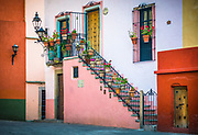 Beautiful staircase at home in Guanajuato, Mexico<br /> ------<br /> Guanajuato is a city and municipality in central Mexico and the capital of the state of the same name. It is part of the macroregion of Bajío. It is in a narrow valley, which makes its streets narrow and winding. Most are alleys that cars cannot pass through, and some are long sets of stairs up the mountainsides. Many of the city's thoroughfares are partially or fully underground. The historic center has numerous small plazas and colonial-era mansions, churches and civil constructions built using pink or green sandstone.<br /> <br /> The origin and growth of Guanajuato resulted from the discovery of minerals in the mountains surrounding it. The mines were so rich that the city was one of the most influential during the colonial period. One of the mines, La Valenciana, accounted for two-thirds of the world's silver production at the height of its production.<br /> <br /> The city is home to the Mummy Museum, which contains naturally mummified bodies that were found in the municipal cemetery between the mid 19th and 20th centuries. It is also home to the Festival Internacional Cervantino, which invites artists and performers from all over the world as well as Mexico. Guanajuato was the site of the first battle of the Mexican War of Independence between insurgent and royalist troops at the Alhóndiga de Granaditas. The city was named a World Heritage Site in 1988.