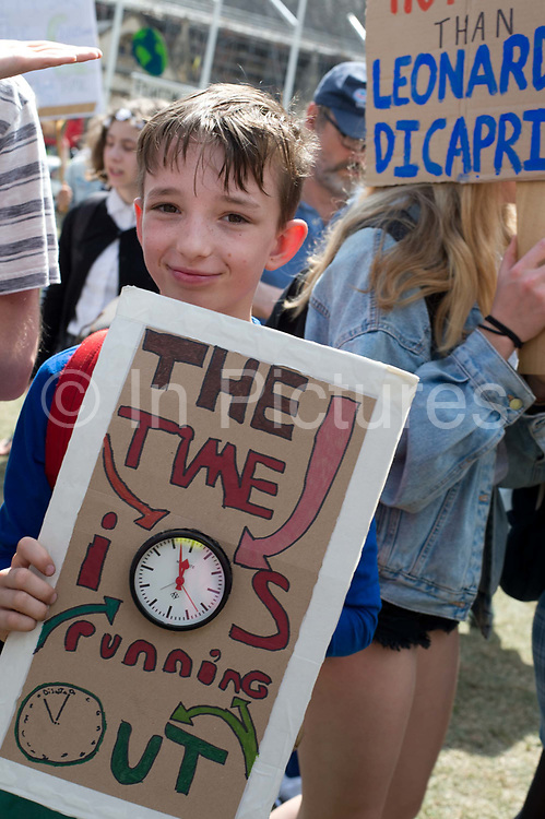 School Climate Strike, London, England, UK. A boy holds a clock set at two minutes to midnight with the words time is running out.