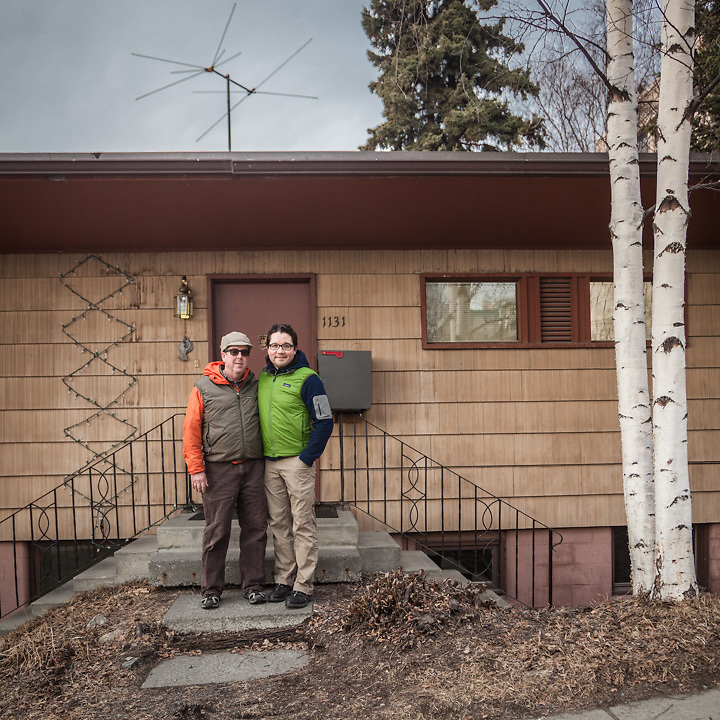 """Glen Hemingson (orange) and Ricardo Lopez in front of their house on Fifth Avenue near Elderberry Park in Anchorage.  """"I moved to Anchorage the day before Thanksgiving in 2002.  In the summer of 2001 I had ridden up here on my BMW motorcycle, and just fell for it.  I had been living in Alta, Utah, a tiny ski town of 400 people, for ten years.  I was looking for a more urban environment, so I moved to Alaska.  I think Anchorage has more going on than just about any other city its size in the country.  And plus, it's so close to Alaska."""" <br />  <br /> """"People here have a wonderful live-and-let-live attitude.  I ran into Frank & Nancy Murkowski a while ago at the grocery store, and said, """"Hello, Governor.""""  He told me they'd just been to Lisa's son's college graduation and then asked me if I knew where the tortillas were.  That kind of thing just doesn't happen anywhere else.""""<br />  <br /> """"I think I'll be here for a while, and don't plan on moving Outside anytime soon.  It's too hot.  I have a good job, a good life and a wonderful partner in Ricardo, whom I love dearly."""" <br />  <br /> """"I really like this town, but one thing I would wish for are more sushi restaurants.  And world peace, of course.""""  <br /> glen@copperwhale.com"""
