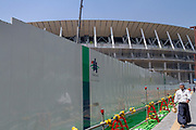 A workmen walks by a construction site wall with the nearly finished new  National Stadium behind. Tokyo, Japan. Monday April 22nd 2019