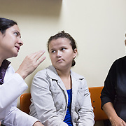 CAPTION: 26-year-old Riccy Nohemy is deaf and dumb. She has to travel for about eight hours to reach Hospital Escuela. She earlier had a surgery to repair her cleft lip. Recently, she also underwent an oral-nasal fistula closure surgery, for which the doctors used flaps. Her mother has accompanied her today, and has even brought a bag of oranges for all the doctors! LOCATION: Hospital Escuela, Tegucigalpa, Honduras. INDIVIDUAL(S) PHOTOGRAPHED: From left to right: Dr Karen Eloísa Medina, Riccy Nohemy Mata and Margarita Mata.