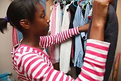 Girl checking out clothes in wardrobe
