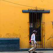 Man walking past a colourful building in Oaxaca, Mexico