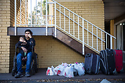 Momen Alsaloum, 22, sits in his father's wheelchair while holding son Amin, 3, at a Days Inn in north Tampa, Florida, U.S. Father and son kept an eye on the family's belongings while waiting for case manager Rana Al Sarraf to help them move to a temporary apartment.