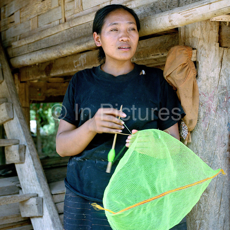 A Khmu woman in Ban Nam Long 'crochets' a traditional bag using synthetic thread outside her house, Luang Namtha Province, Lao PDR. Traditionally, women make the bags by twisting Liana 'jungle' vine to make into a strong fibre and then 'crochet' into a traditional bag used by men and women for carrying items to and from the fields. Liana vine or 'piat' in Lao, is harvested from the forest, although these days it is becoming more difficult to find and many woman now use colourful synthetic thread.