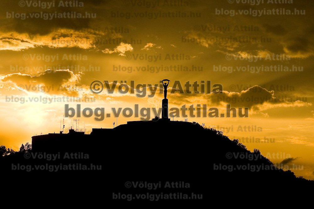 Budapest's Freedom Monument on the top of Gellert hill is silhouetted by the setting sun.