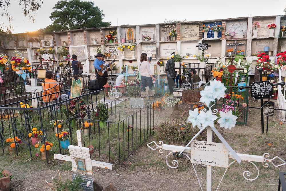 Mexican family visit the graves of a relative in the Nuestra Señora de Guadalupe cemetery during the Day of the Dead festival November 1, 2016 in San Miguel de Allende, Guanajuato, Mexico. The week-long celebration is a time when Mexicans welcome the dead back to earth for a visit and celebrate life.