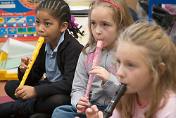 Primary school pupils learning to play the recorder in a music lesson at school,