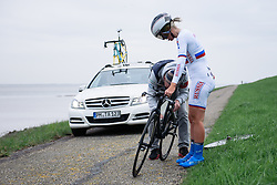 Slow wheel change for Tatiana Antoshina at Omloop van Borsele Time Trial 2016. A 19.9 km individual time trial starting and finishing in 's-Heerenhoek, Netherlands on 22nd April 2016.