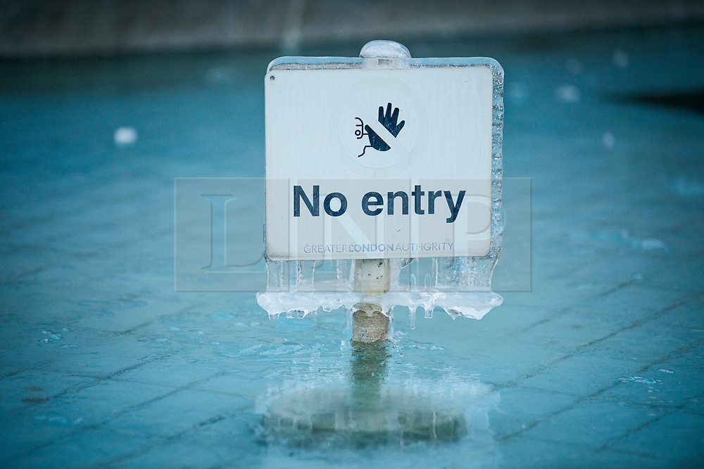 © Licensed to London News Pictures. 13/02/2021. London, UK. A sign covered in ice in the fountains at Trafalgar Square in central London which remain frozen over following another night of sub zero temperatures in the capital. Photo credit: Ben Cawthra/LNP