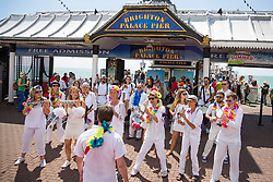 © Licensed to London News Pictures. 23/07/2017. Brighton, UK. Members of a drum band play in front of the Brighton Palace Pier. Photo credit: Hugo Michiels/LNP