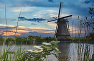 A picturesque windmill at sunset in the Dutch countryside.