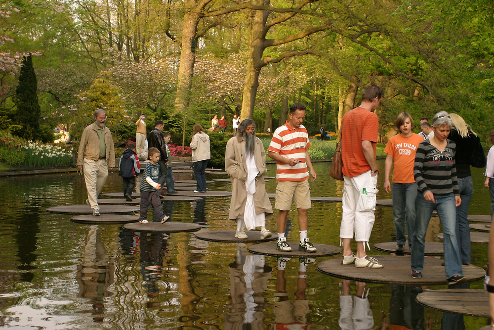 Tourists walking on wooden stepping stones. Springtime in the Keukenhof  gardens, Lisse, the Netherlands.<br /> Also known as the Garden of Europe, is one of the world's largest flower gardens.