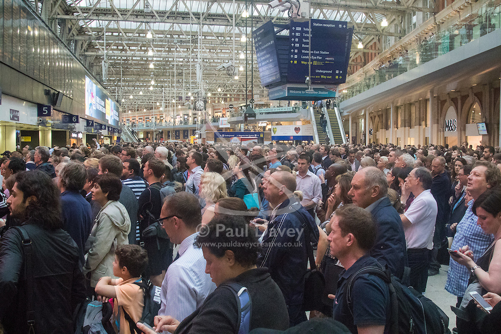 "Waterloo Station, London, June 23rd 2016. Commuters face severe delays at London's Waterloo Station as bad weather causes power failures across the rail network. PICTURED: Thousands of commuters await the ""cancelled""  notices to change."