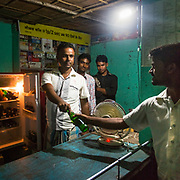 CAPTION: Shahjahan Mobile Plaza, a recent convert from diesel to energy derived from biomass by DESI Power, gives parched customers an opportunity to quench their thirst thanks to its fridge stocked with cold drinks. LOCATION: Bara, Araria District, Bihar, India. INDIVIDUAL(S) PHOTOGRAPHED: From left to right - Imran Alam, Mohammad Kainan Alam, unknown (but distant) and Imtiaz Ahmad..