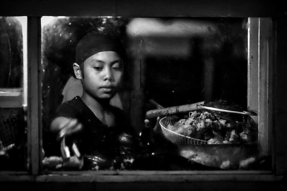 """Portrait of a boy frying chicken in a """"kaki lima"""" for sale in a local market in Indonesia. The image is shot at night through the greasy glass of the food cart to emphasise the lack of hygiene in these rural communities."""
