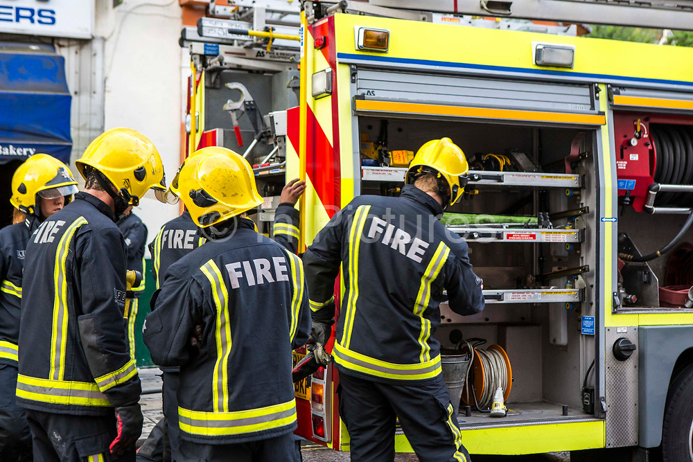 Firefighters from the London Fire Brigade gather by their fire engine as they respond to an emergency on Church Street, Stoke Newington, London.  They have been called out due to a large explosion in the basement of a shop.  The London Fire Brigade is the 4th largest fire-service in the world.