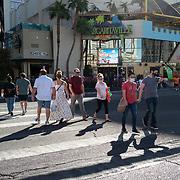 People wearing masks walk across The Strip in Las Vegas, Nevada on Saturday, October 17, 2020. (Alex Menendez via AP)