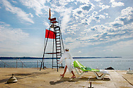Sunbathers preparing a sun bed on a sea terrace. Piran , Slovenia Visit our PHOTO COLLECTIONS OF SLOVANIAN  HISTOIC PLACES for more photos to download or buy as wall art prints https://funkystock.photoshelter.com/gallery-collection/Pictures-Images-of-Slovenia-Photos-of-Slovenian-Historic-Landmark-Sites/C0000_BlKhcYWnT4Sites/C0000qxA2zGFjd_k