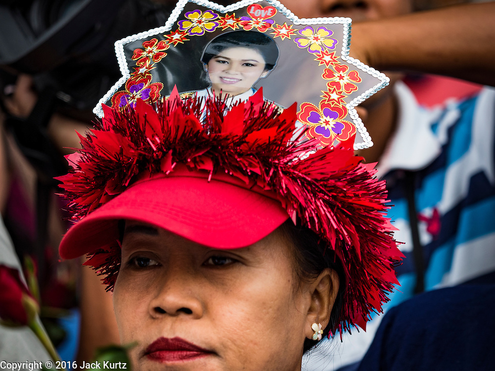 05 AUGUST 2016 - BANGKOK, THAILAND: A supporter of Yingluck Shinawatra, wearing a hat with a photo of Yingluck, waits for her to arrive at the Supreme Court in Bangkok. Yingluck appeared in court of Thailand Friday to start her legal defense. She was deposed by a military coup in 2014 and is being tried on corruption and mismanagement charges related to a price support plan for Thai rice farmers that was instituted while she was Prime Minister. More than two years after her government was deposed by a military coup, she is still a popular figure and hundreds of her supporters packed the area around the courthouse to greet her when she arrived at the Court.        PHOTO BY JACK KURTZ
