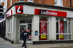 © Licensed to London News Pictures. 14/06/2020. London, UK. A man walks past a branch of Ladbrokes in north London, which will reopen on 15 June as coronavirus lockdown restrictions are eased. The government has announced that all betting shops can re-open on Monday 15 June. Betting shops were closed late March following outbreak of COVID-19. Photo credit: Dinendra Haria/LNP