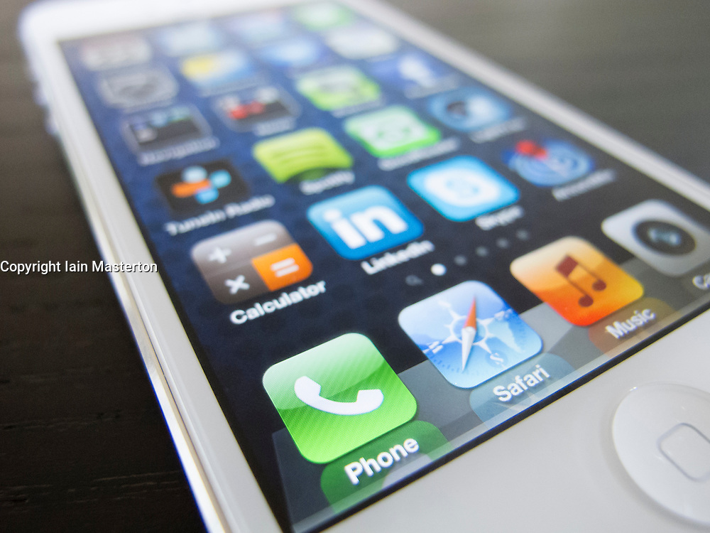 Detail of new iPhone5 smart phone screen showing many homescreen apps