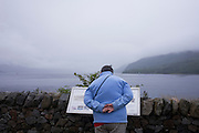 Tourist reads information sign on wintry evening on Inverscaddle Bay, Ardgour, Scotland.