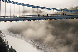 © Licensed to London News Pictures; 22/11/2020; Bristol, UK. People cross the Clifton Suspension Bridge over the Avon Gorge with mist during the Covid-19 lockdown in England during the coronavirus pandemic as the UK Government tries to stop the spread of the covid-19 coronavirus pandemic. Bristol now has one of the highest rates of Covid-19 infection in the country. Photo credit: Simon Chapman/LNP.
