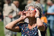 Middletown, New York - A woman uses eclipse glasses to watch a partial solar eclipse on Alumni Green at SUNY Orange on Aug. 21, 2017.