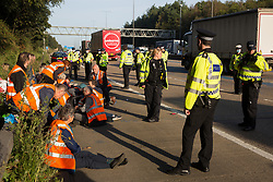 Ockham, UK. 21st September, 2021. Surrey Police officers monitor Insulate Britain climate activists who had previously blocked the clockwise carriageway of the M25 between Junctions 9 and 10 as part of a campaign intended to push the UK government to make significant legislative change to start lowering emissions. Activists briefly halted traffic on both carriageways of the motorway before being removed and arrested by Surrey Police.