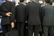 businesspeople  in black suits and briefcases standing listening